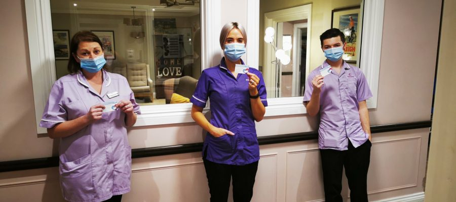 Members of the Encore Care Homes team with their post-Covid 19 vaccine cards